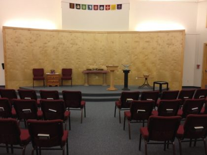 Our Sanctuary: facing an elevated worship and performance area. There are small hooks on this wall that allow art, signs, or anything else to be hung and displayed.